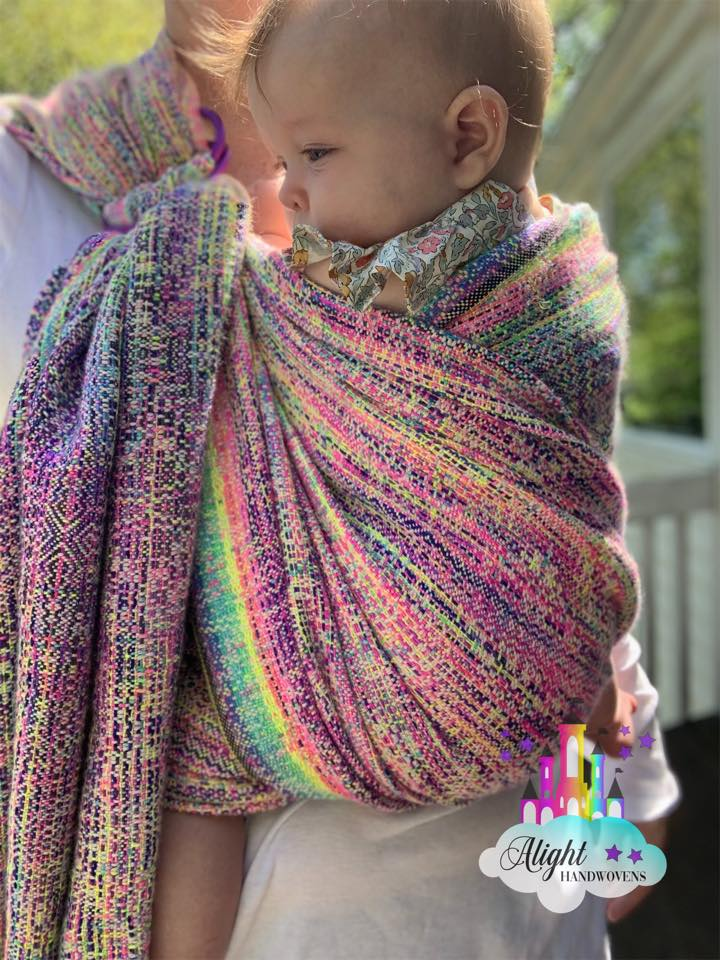 Semi Front Wrap Cross Carry  photo ID: a baby girl is wrapped on her mother's front in a pastel rainbow ring sling. They are standing outside on a porch and the Alight Handwovens watermark is in the bottom right corner.