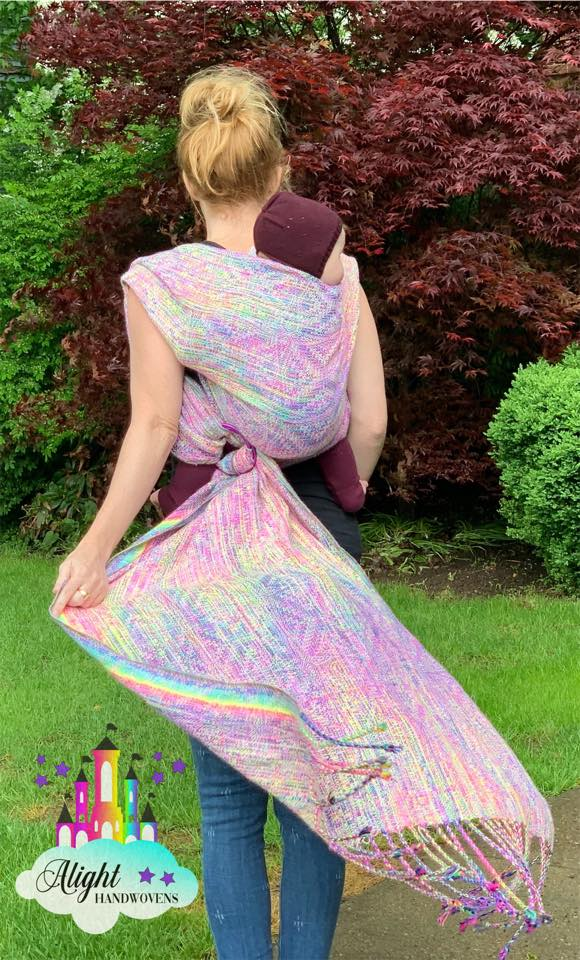 Rucksack  photo ID: a baby girl is on her red haired mother back in a pastel rainbow ring sling. They are standing outside and trees are a blurry background. The alight Handwovens watermark is in the left corner.