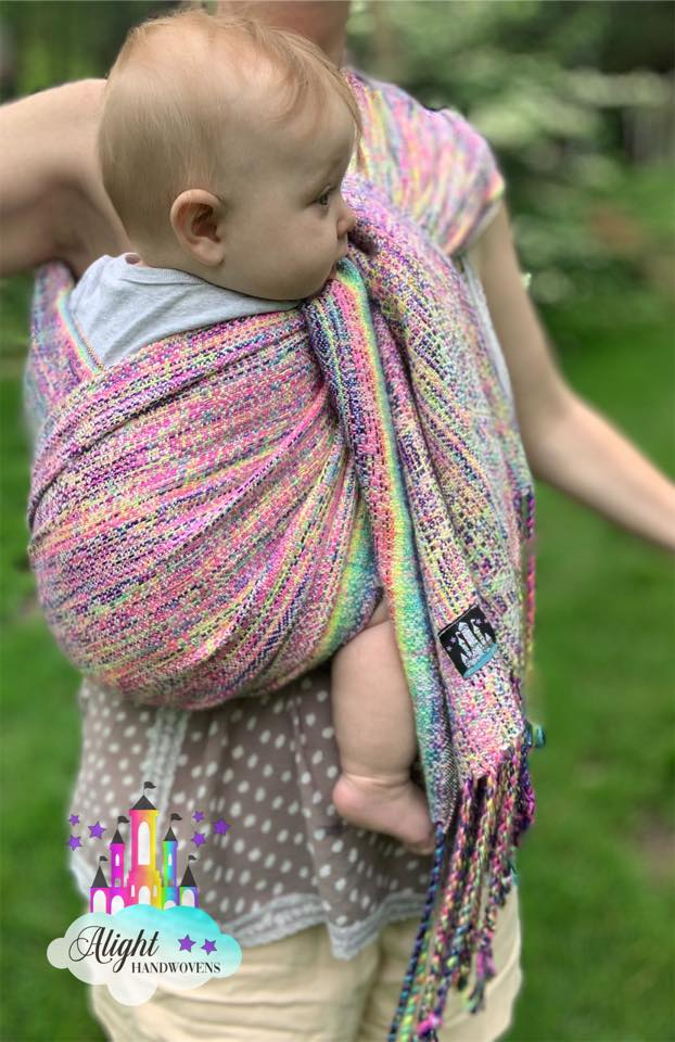 Coolest Hip Cross Carry  photo ID: a baby girl being worn on her mother's hip in a pastel rainbow ring sling. The alight Handwovens watermark is in the left corner and they are standing outside in the grass.