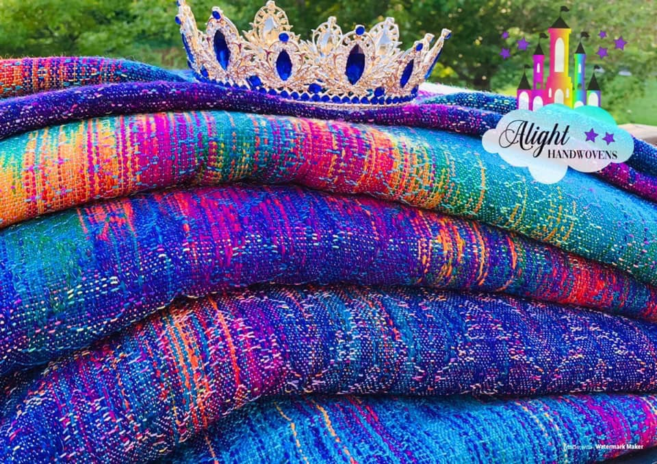 Photo ID: a stack of beautiful blue rainbow wraps with a crown sitting on top. There are trees in the background and the alight Handwovens watermark in the top right corner.