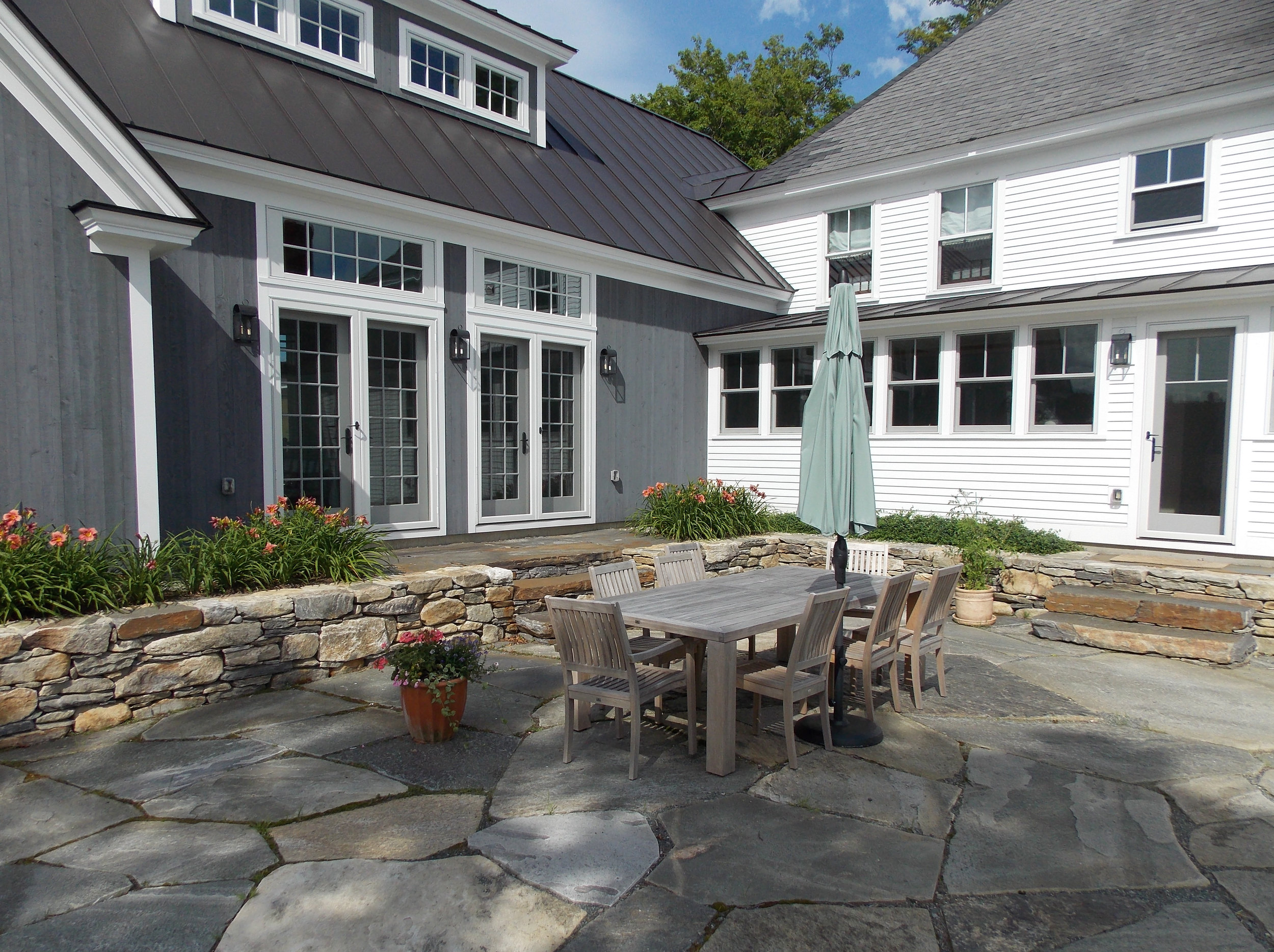 About 1,500 square feet of native Vermont fieldstone was installed for the patios and walkways, including the main terrace at the rear of the property (foreground) and the sunken viewing terrace (background, left). The two spaces are separated by an amsonia hedge and small wall.