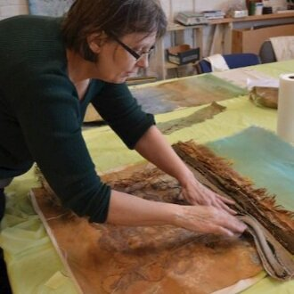 Deborah Foutch works with mixed media and fiber to create one of her pieces of soil conservation art.