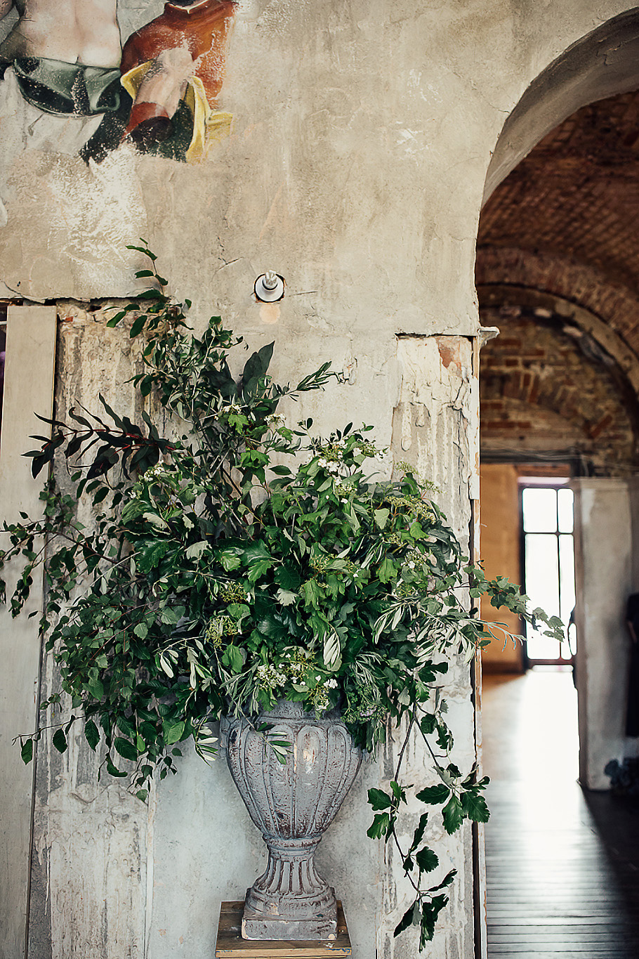 Foliage only urns flanking the entrance to the decaying romantic reception building