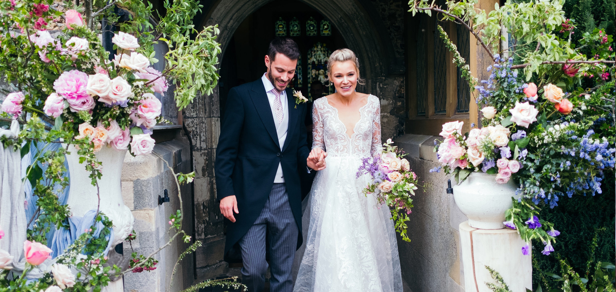 Charlotte and Rob steeping out of the Church on their family home grounds in Essex.