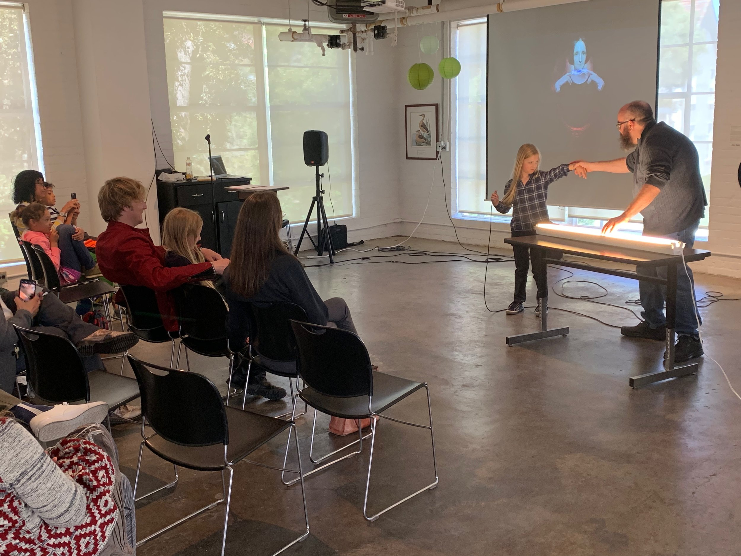 """Artist Matthew Weedman and an audience member demonstrate how to turn a light bulb into a musical instrument at Weedman's performance """"It's Alive!"""" in the Grabhorn Institute gallery, Summer 2019."""