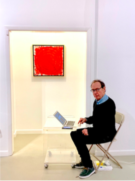 Art critic and artist, Anthony Haden-Guest, writing a review for J. Steven Manolis' solo painting exhibition,  Palm Beach Light , sitting in the Fritz Gallery. Painting pictured: J. Steven Manolis,  REDWORLD Concentric , 2019.01, Acrylic on canvas, 24 x 24 in.