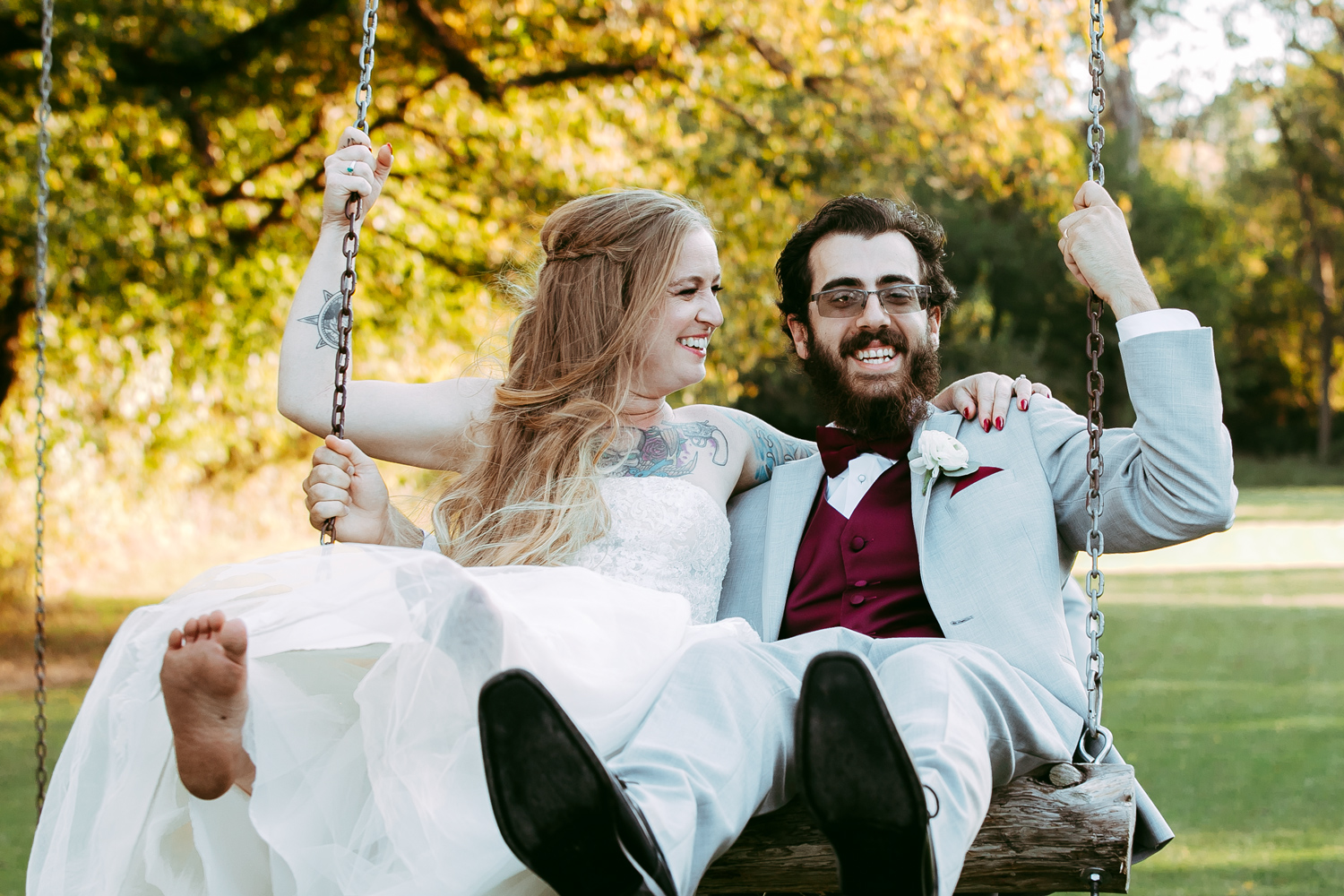 Summer wedding photo of bride and groom sitting on a swing at Ranch of the Saints in Oklahoma by Amanda Lynn.