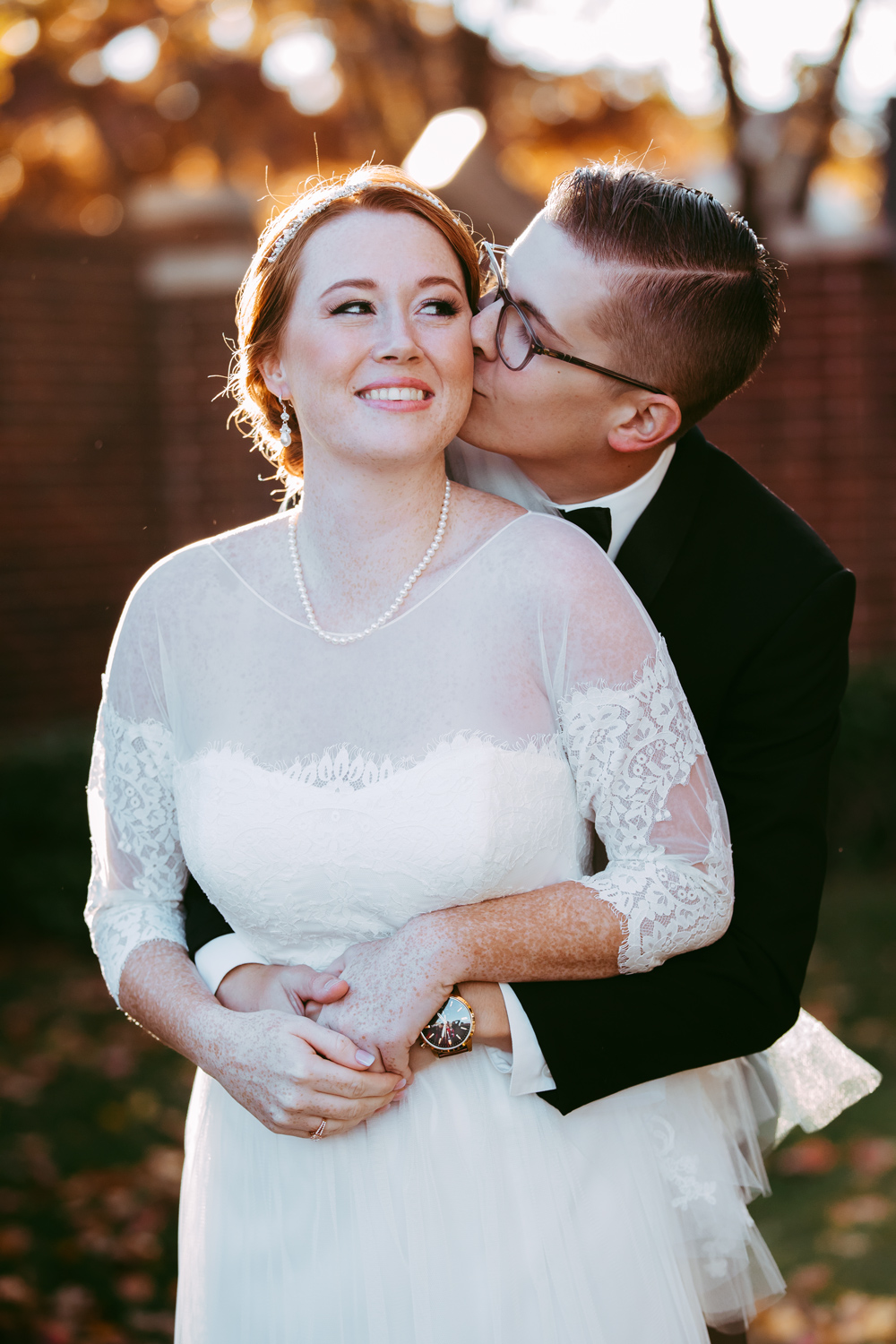 Groom embracing bride and kissing her on the cheek at a fall wedding in Oklahoma by Amanda Lynn Photography.