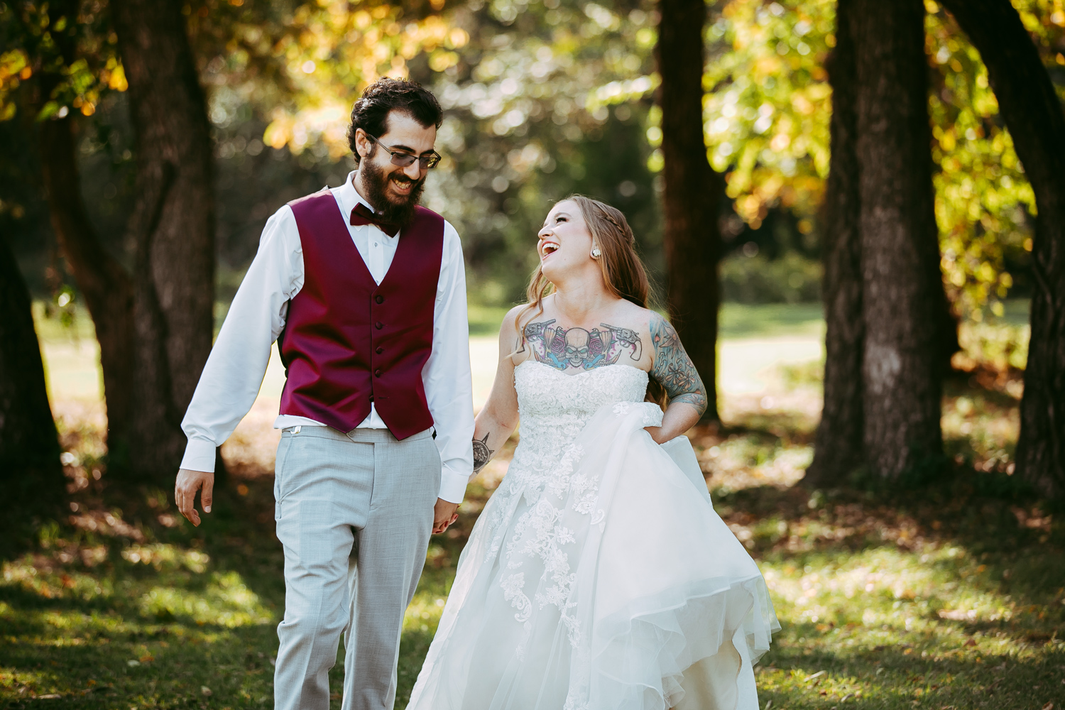 Bride and groom walking and laughing together in an open park in the fall in Oklahoma by Amanda Lynn.