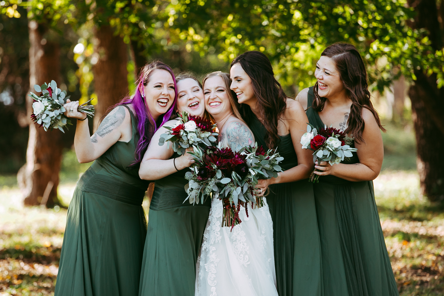 Oklahoma summer wedding, image of bride with her bridesmaids, wearing long green dresses at Ranch of the Saints by amanda Lynn.