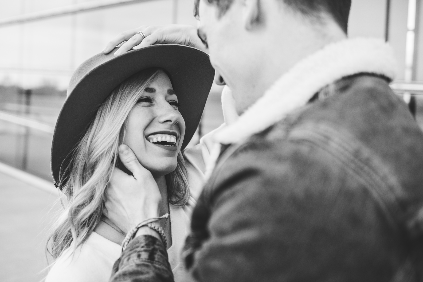 Black and white image of girl wearing a hat laughing while guy pulls her closer to him in Oklahoma City.