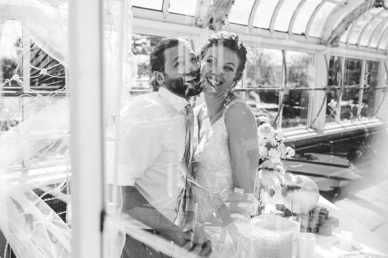 Black and white fun images of bride and groom thru a window at the Will Rogers Park greenhouse in OKC by Amanda Lynn Photography.