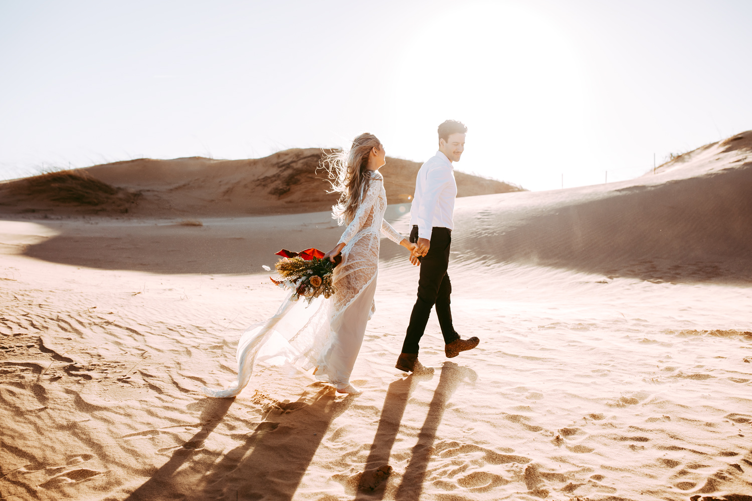Bride and groom walking on sand at the Little Sahara State Park in Oklahoma by Amanda Lynn Photography.