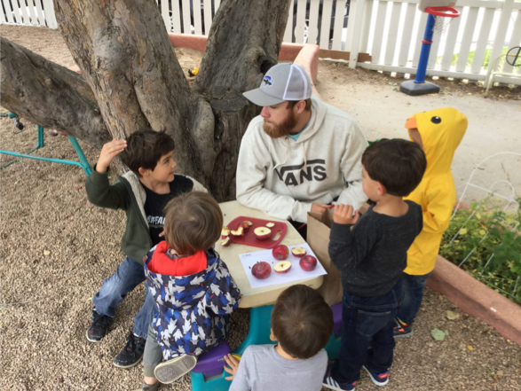 Student Dustin Bailey shares apple sampling with local preschool students.