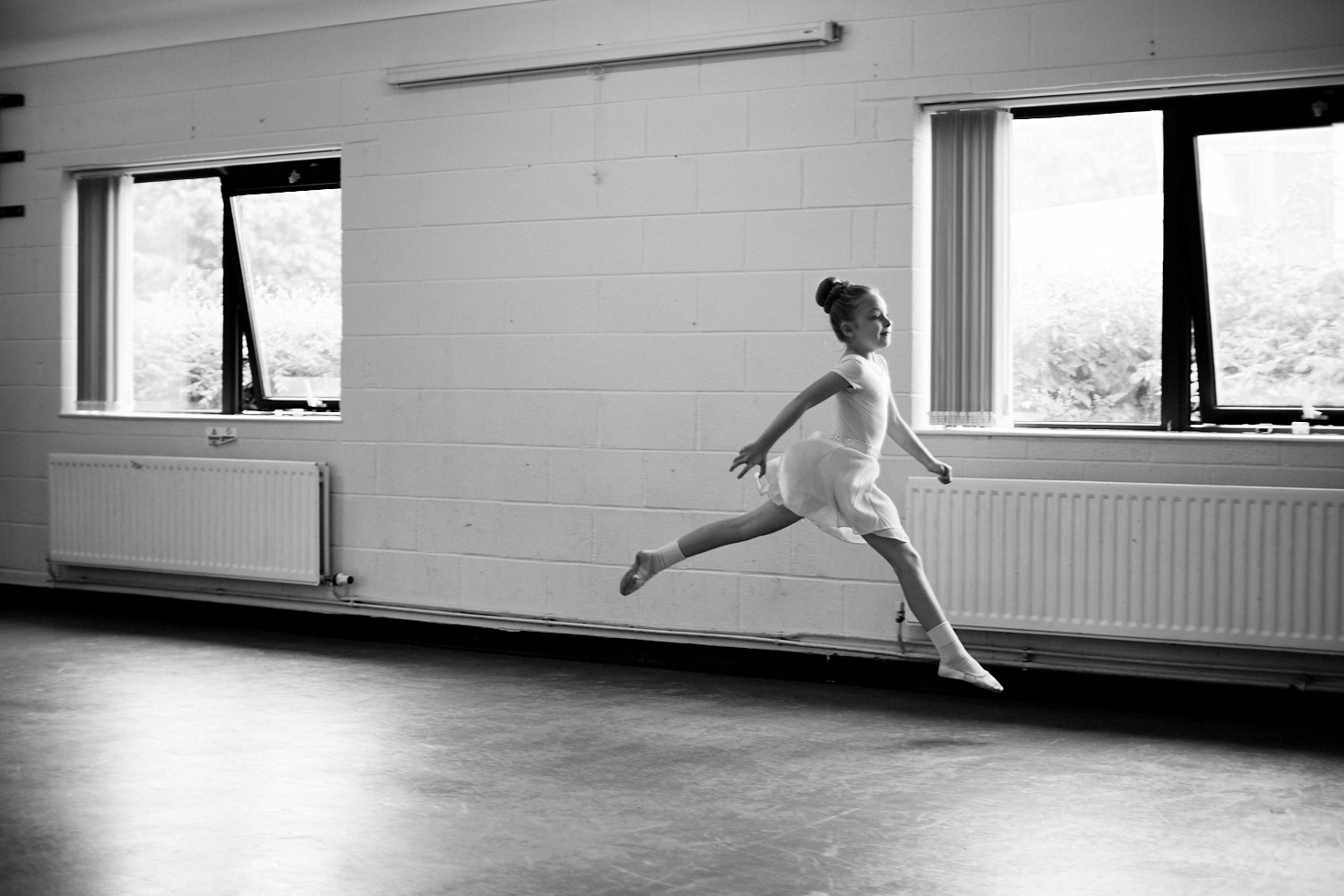 A young ballet dancer leaping through the air in black and white