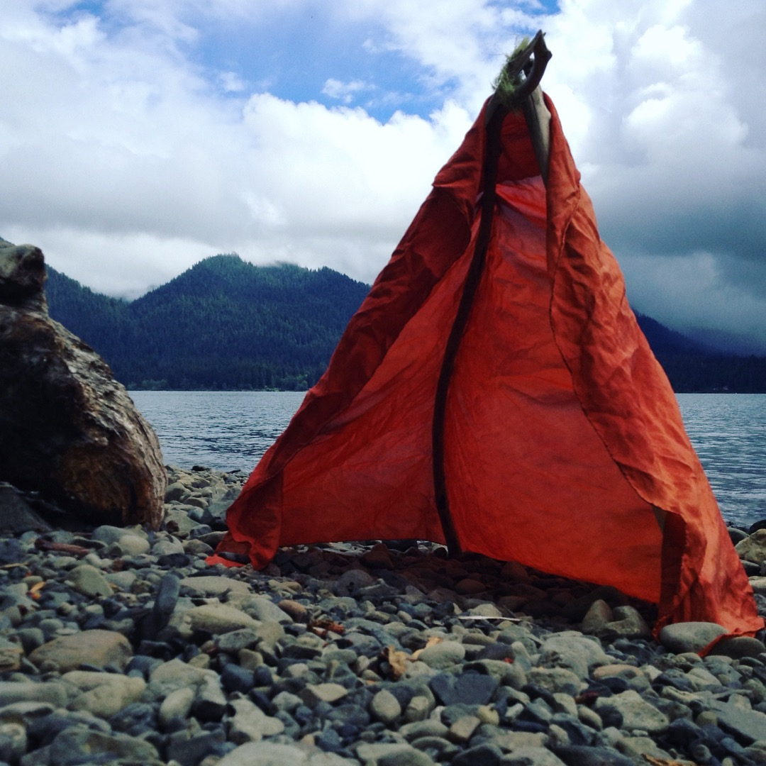 A Red Tent on the shore of Lake Quinault. Part of the series of ephemeral outdoor installations utilizing site specific sticks and a madder dyed silk. Representing the confluence of Woman and Nature, made during menstruation.