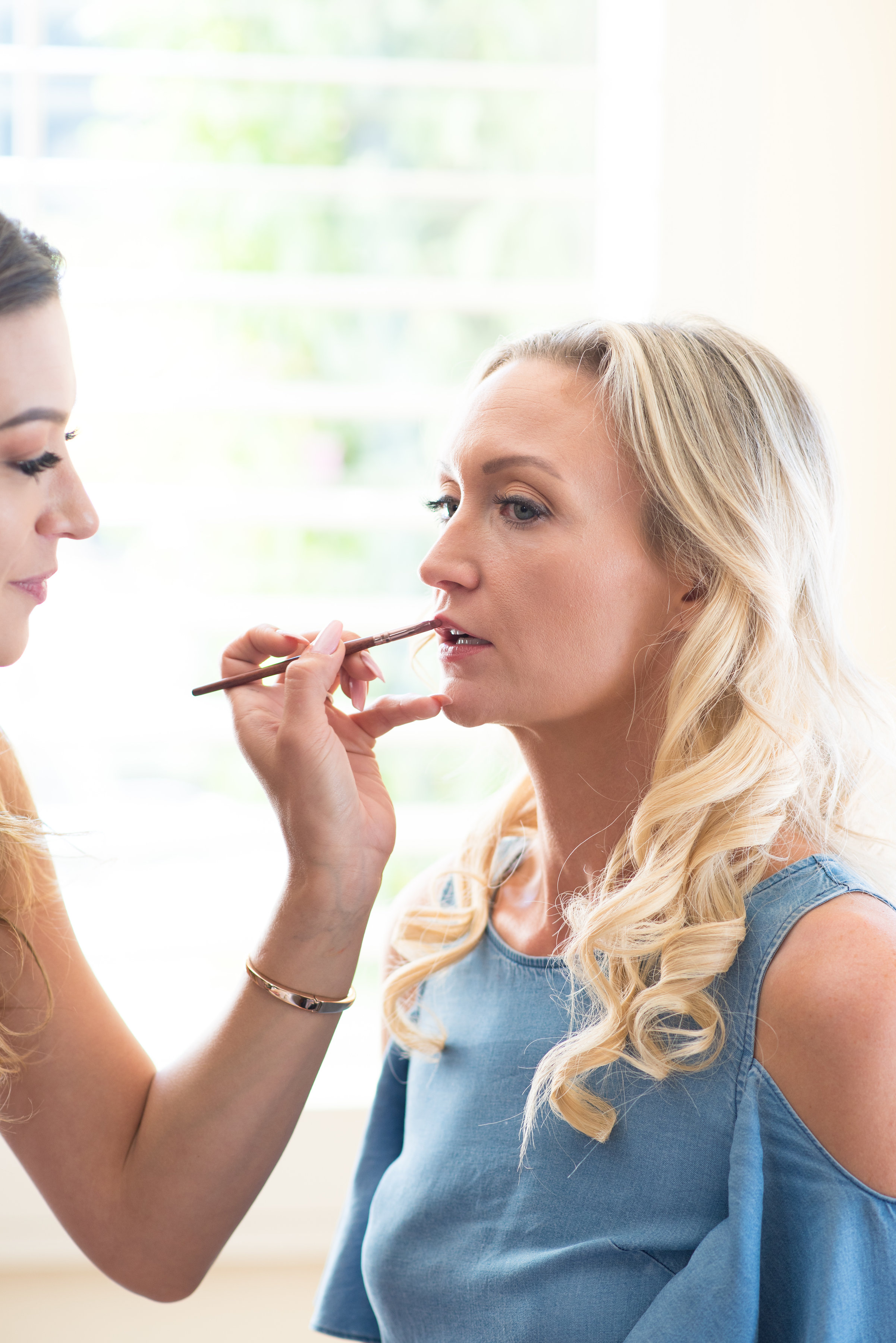 Using a very small lip brush on the bride-to-be, Stephanie for her lips. Precision is key.