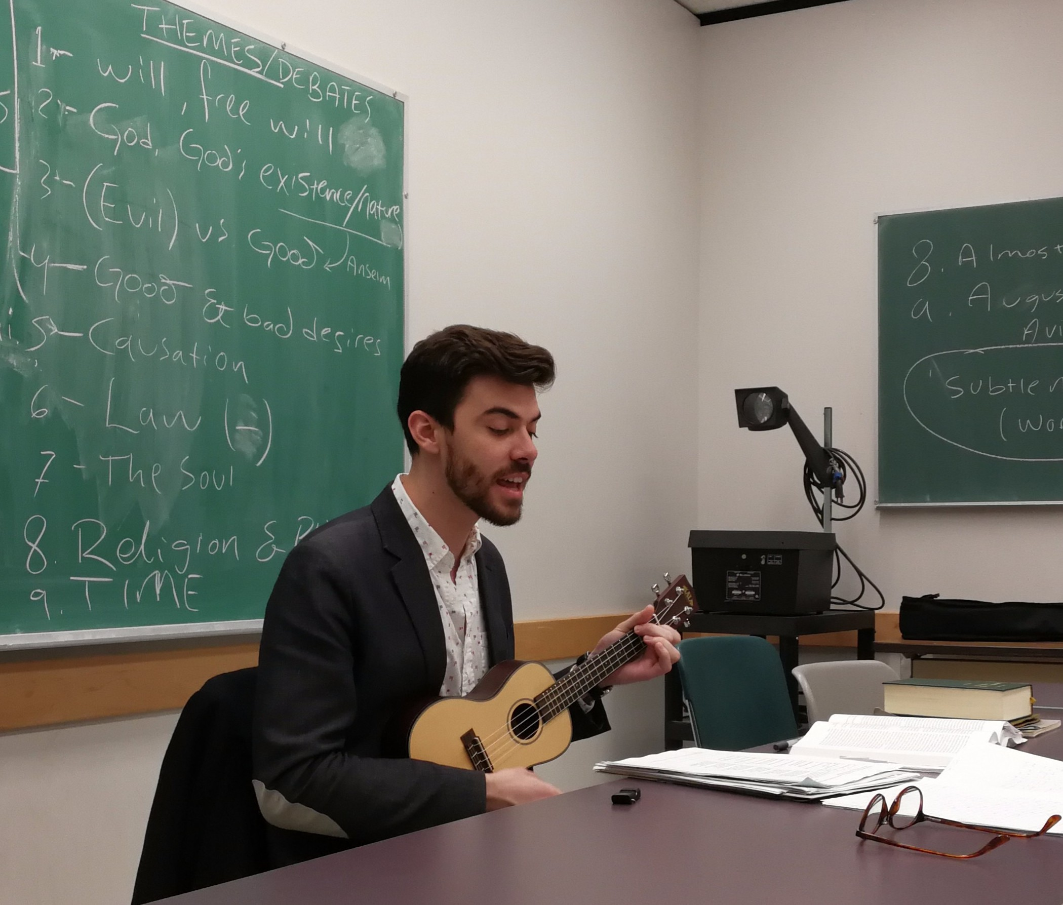 """Singing a song I wrote to help my students study: """"Early Medieval Philosophy (For Course of Same Name)"""" .  Here are the   lyrics     (—link opens in a new tab)."""