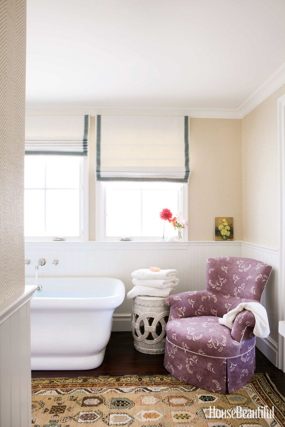 Bathroom   An armchair, a ceramic stool, an aged Persian rug, wallpaper, and Roman shades create a sitting room atmosphere in Susan Croul's bathroom. Dunham's KP Armchair in Carolina Irving Mimosa Vine, from  Hollywood at Home .  Ralph Lauren  herringbone wallpaper.