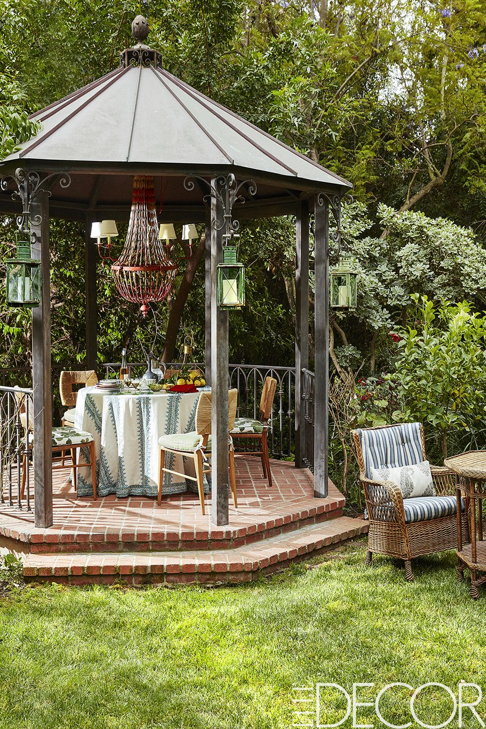 The gazebo's dining chairs, vintage French chandelier and lanterns are from   Hollywood at Home   ; the tablecloth and the chair cushions are of fabrics from   Peter Dunham Textiles   .