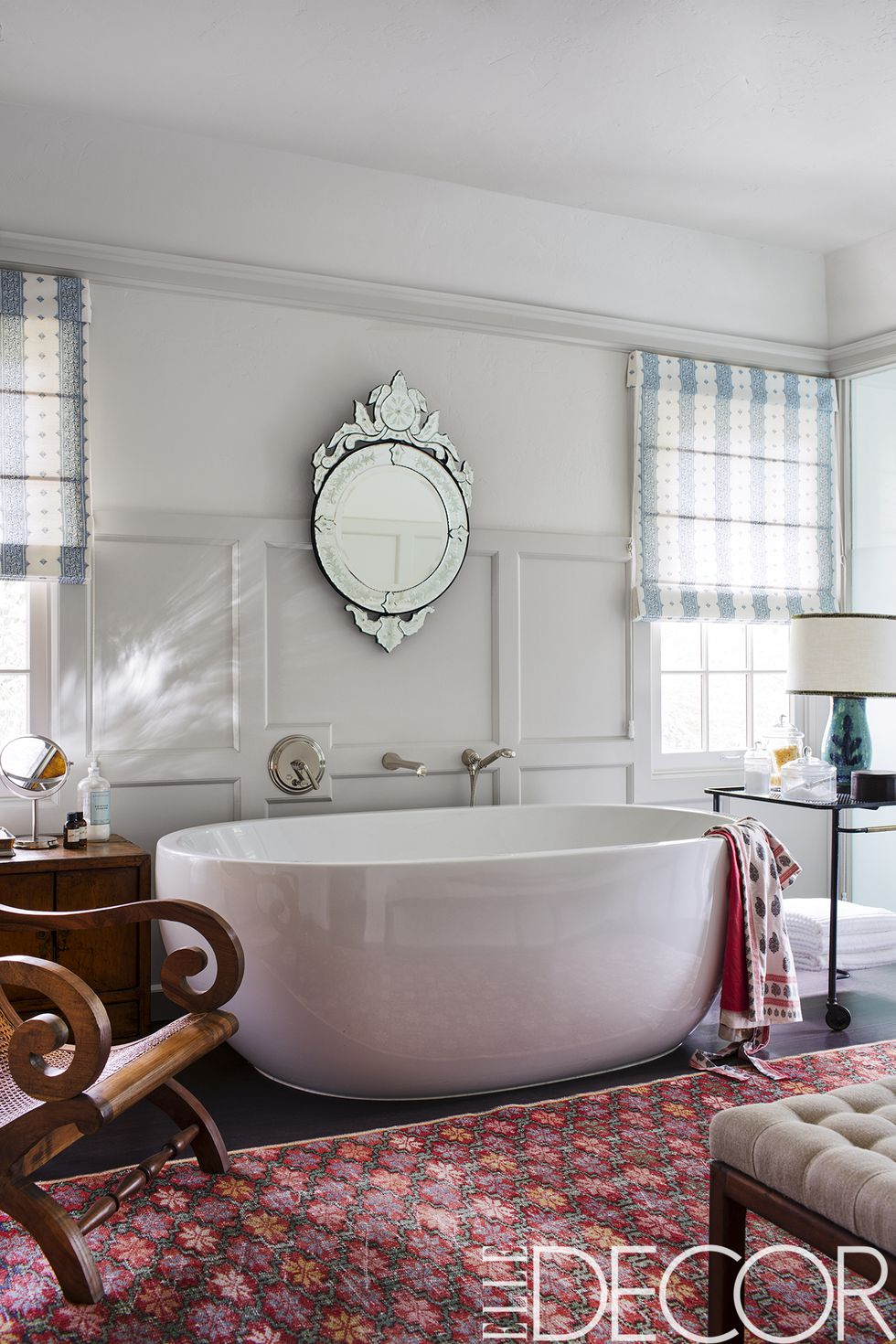 The master bath features a Venetian mirror, a 1950s bar cart by    Mathieu Matégot   , and a vintage rug, the flooring is oak and the walls are painted in    Benjamin Moore's Navajo White   .