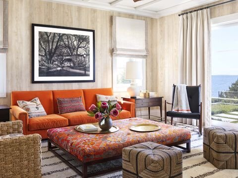"""Orange is a great color that's not hot like red,"" says Dunham, who added a tiny bit as trim on the window treatments to play off the sofa.  Wallcovering:  Nobilis.  Sofa,   pillows,  and  ottoman:  Hollywood at Home (sofa in a Pindler fabric and ottoman in vintage textile).  Floor poufs:  Mecox.  Window shades:  Pindler."