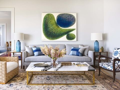 Blues and sandy ochers enhance the sea hues beyond the windows.  Wall art:  1970s, RE Steele Antiques in East Hampton.  Armchairs:  Hollywood at Home.  Lounge chair:  Mecox.  Lamps: Natan Moss for Hollywood at Home.  Paint:  Simply White, Benjamin Moore.