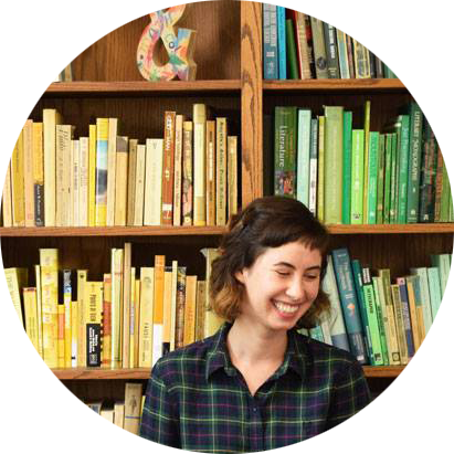 Woman_In_Front_Of_Colorful_Bookshelf.png