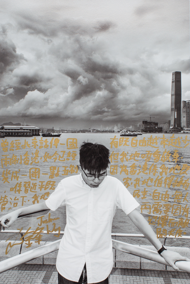 """Joshua Wong, activist and politician, Admiralty, Hong Kong, July 5, 2018. Written July 4, 2019.  Transcription and translation of handwriting:  曾經北京話俾一國兩制香港,如今已經變成一國一點五制,喺習近平管治下,我地有既自由越來越少,但我地唔會放棄,因為香港係我地既家,我地值得擁有民主、自由,無人再需要因為恐懼要離開呢度。 (Once, Beijing promised Hong Kong """"One Country, Two Systems,"""" but it has become """"One Country, 1.5 Systems"""" now. Under Xi Jinping's rule our freedom has been eroding, but we will never give up because Hong Kong is our home. We deserve democracy and freedom. No one should have to flee their home out of fear.)"""