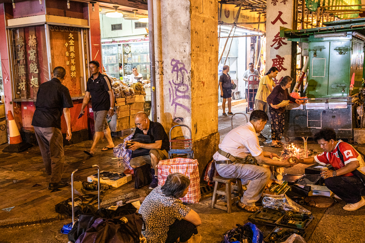 Traders outside Pei Ho market and an elderly woman burns paper offerings to appease the ghosts.