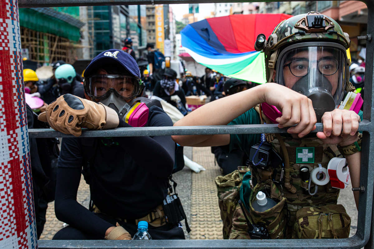 A medic and protestor await tear gas and police operations to sweep the area in Sham Shui Po. The medics uniform and the expression in her face, her age was compelling to me.