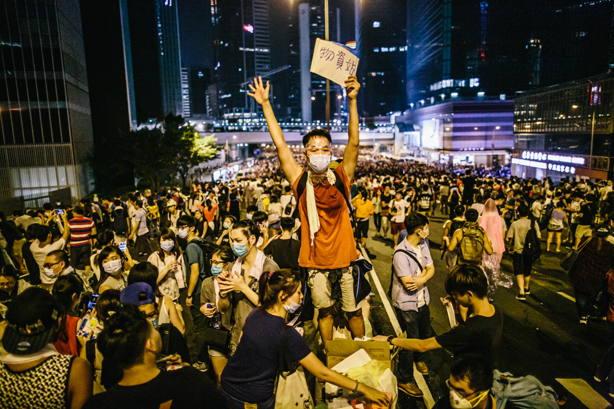 """14.09.28 - Hong Kong: Protestors outside the government's headquarters in Admiralty have taken over Harcourt Rd. Police conduct a clearance operation using tear gas. A man holds up a sign saying """"supplies'."""
