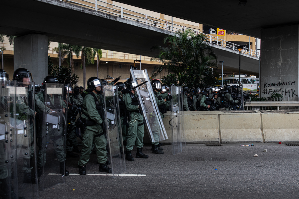 19.08.24 - Riot police take cover under a highway.