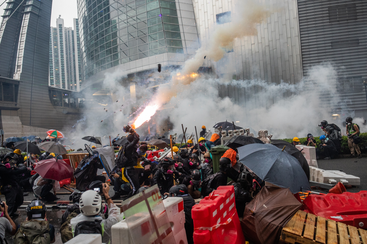 19.08.25 - Tsuen Wan, Hong Kong - An anti-government protestor jumps to catch a tear gas grenade as it explodes.