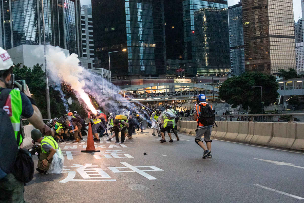 Tear gas grenade explodes over journalists.