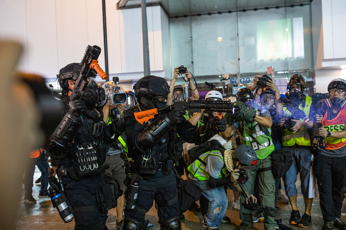 Cops shooting rubber bullets while journalists look on with genuine facial expressions.