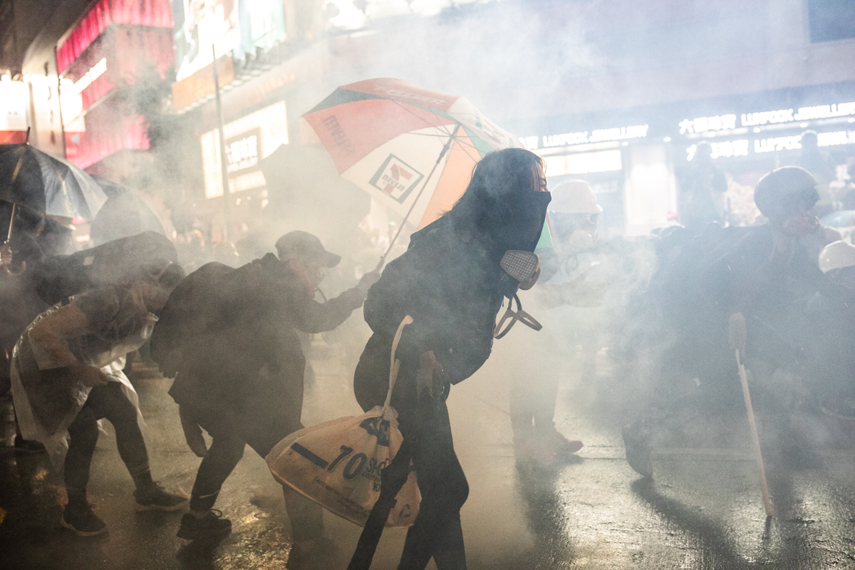 Protestor with no mask on in tear gas cloud.