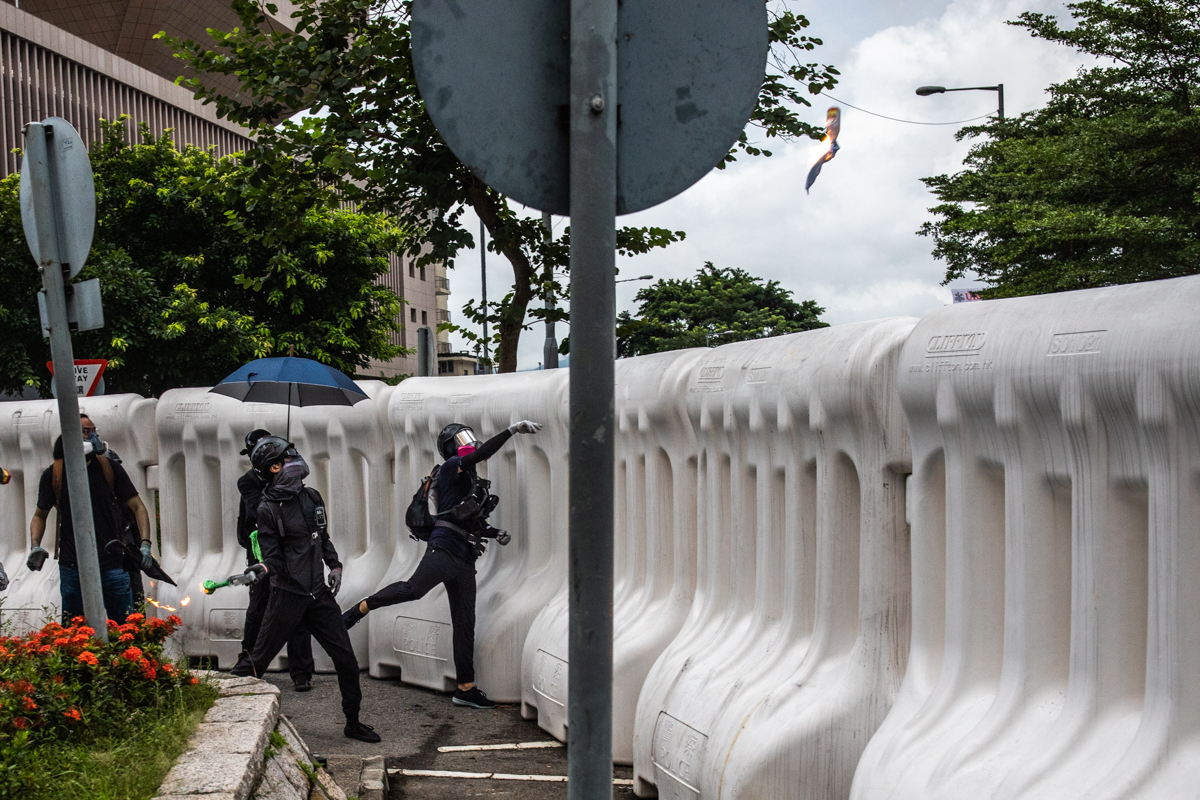 Protestors lobbing petrol bombs over the water barricades at government hq in Admiralty