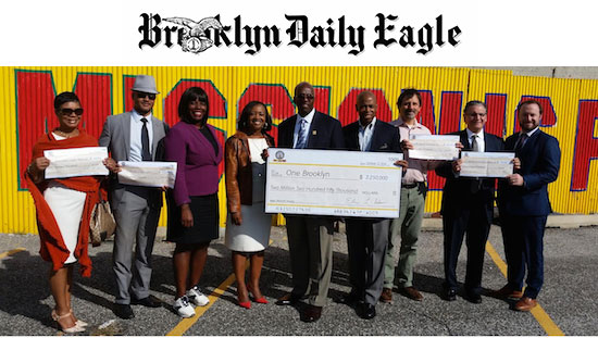 Brooklyn Borough President Eric Adams, fourth from right, and several elected officials, community activists and developers' representatives display a mock check for $2,250,000 as Adams announces his Faith-based Development Initiative in the parking lot of Calvary Community Church in Crown Heights. Eagle photo by James Harney