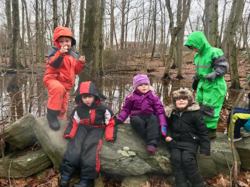 Forest Preschool children playing on the stone wall near the Con Edison STEM Challenge Course.