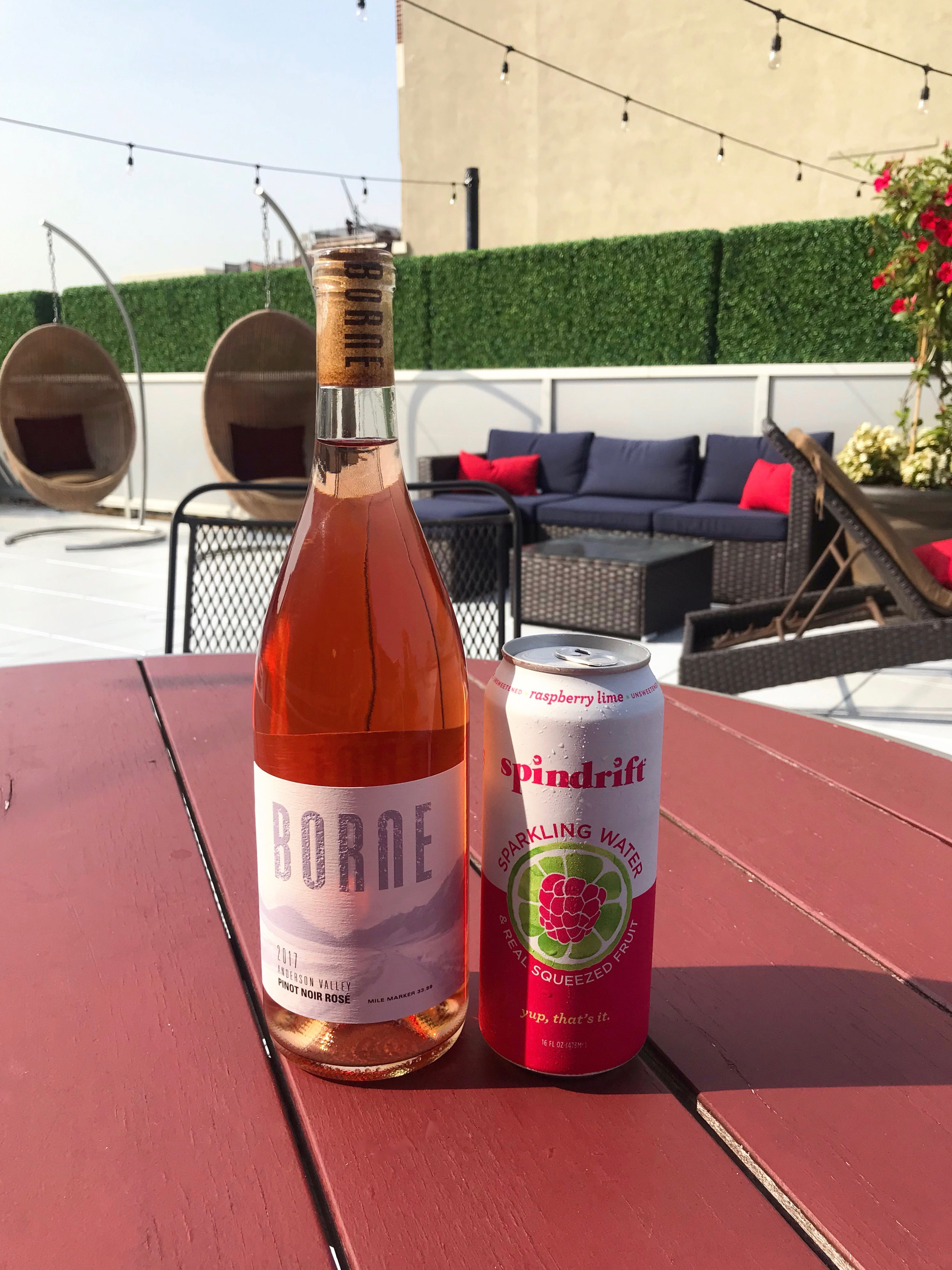 Image of bottle of rosé and can of Spindrift on red wooden table on sunny rooftop with patio furniture and string lights