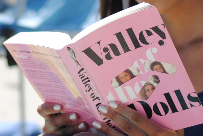 Close-up photo of the novel  Valley of the Dolls  being read on the beach