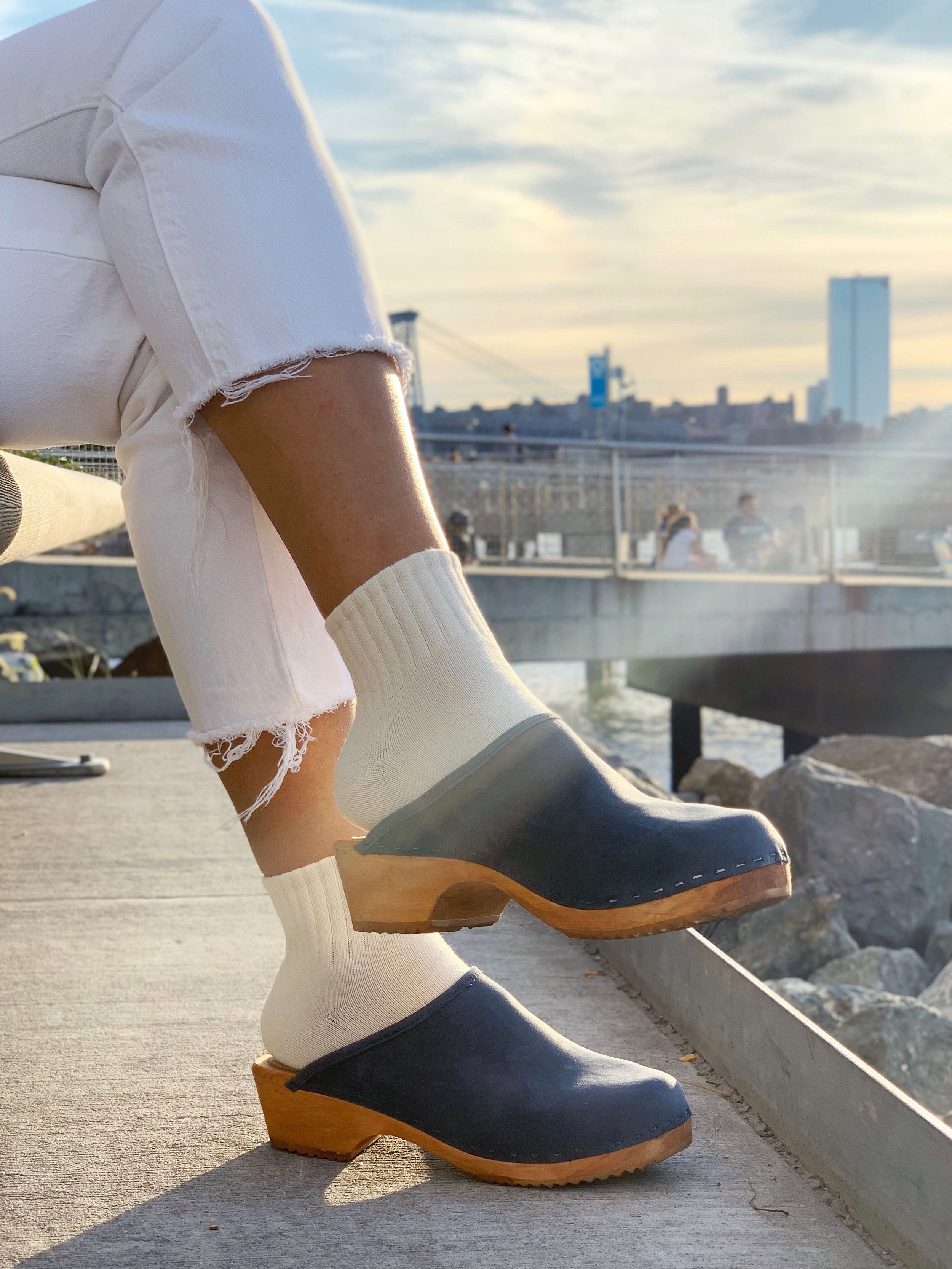 White jeans, cream socks, and dark blue Tessa clogs photographed in front of city skyline/waters edge