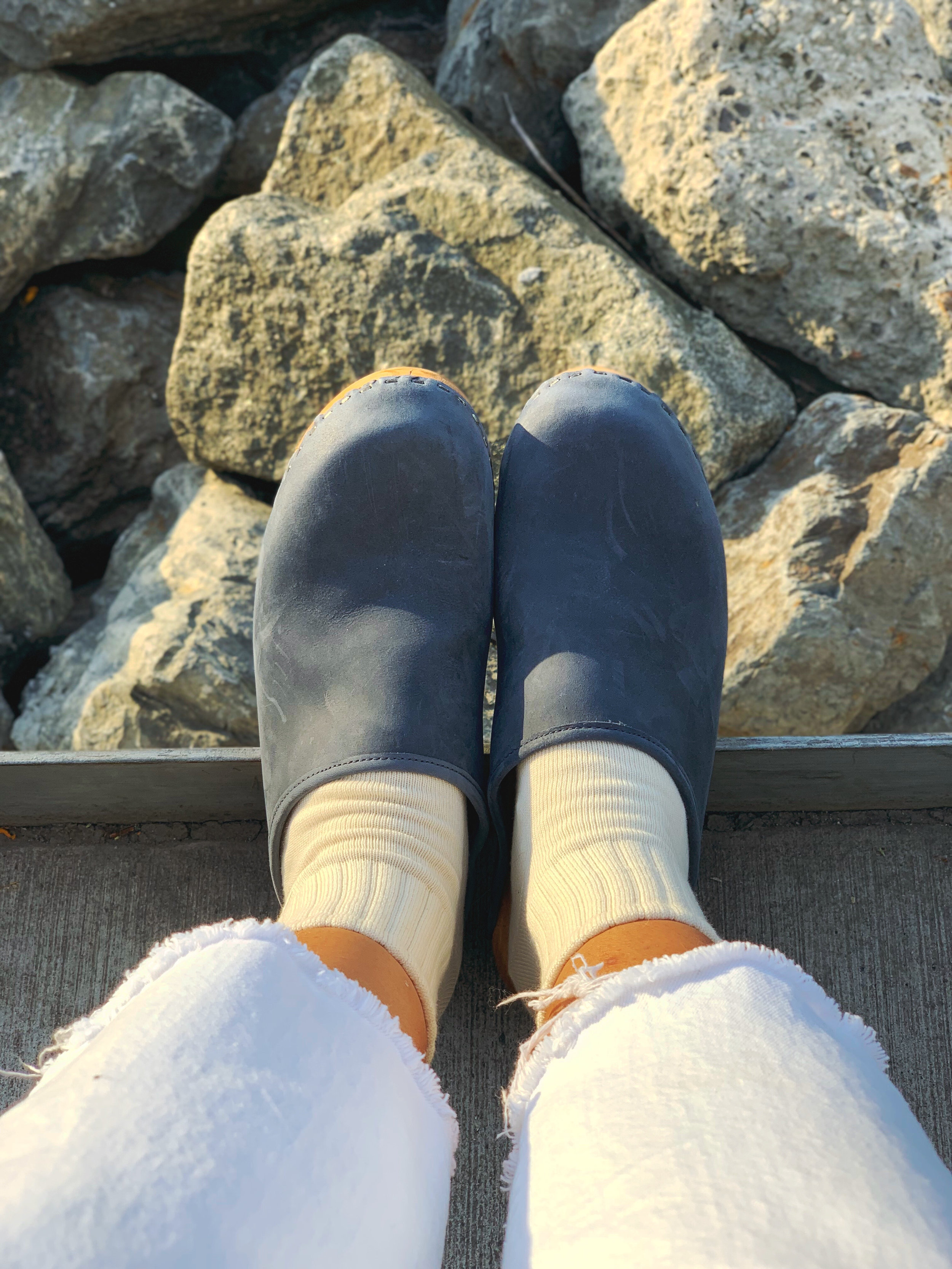 Dark blue clogs, cream socks, white jeans, in front of rocks at water's edge
