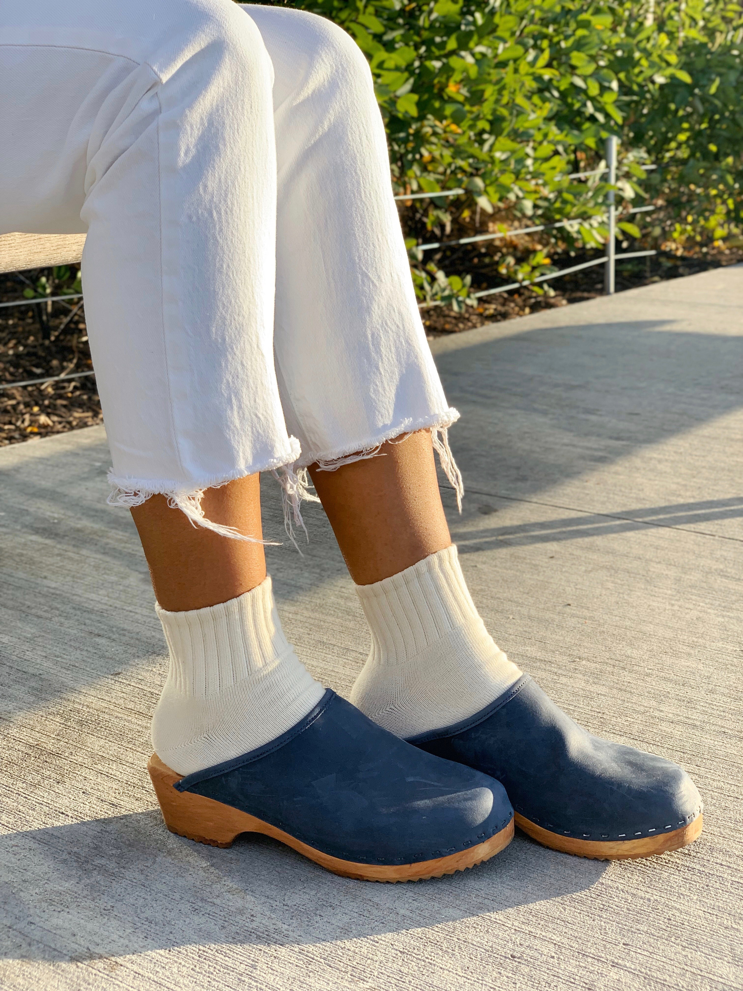 Dark blue clogs, cream socks, white jeans shown outside in city park