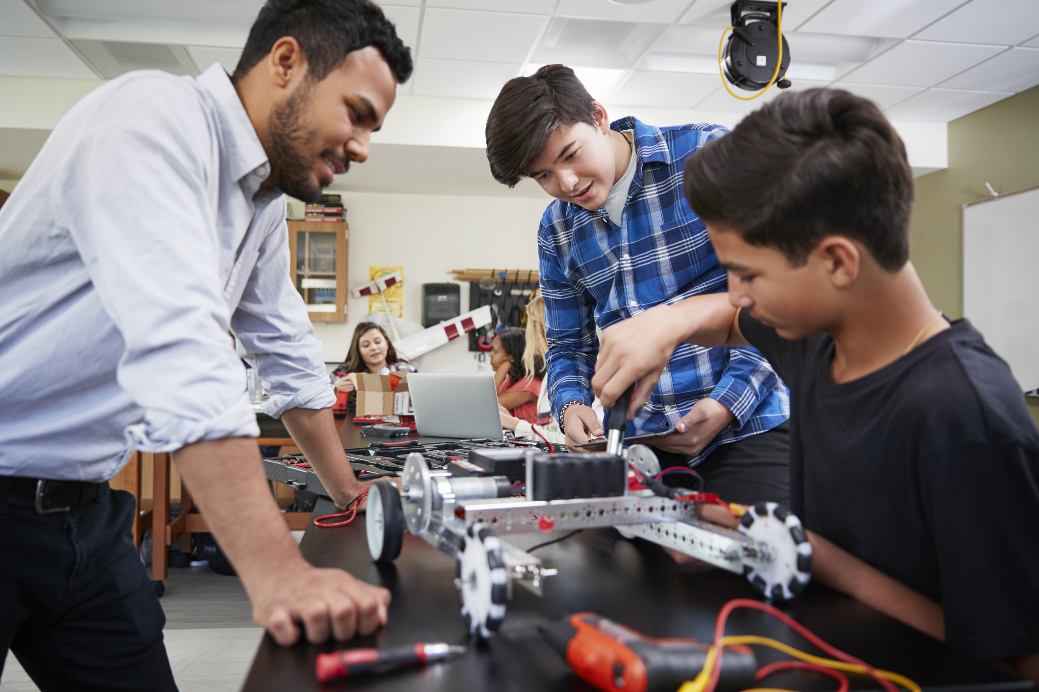 Teacher and students working on a robot.