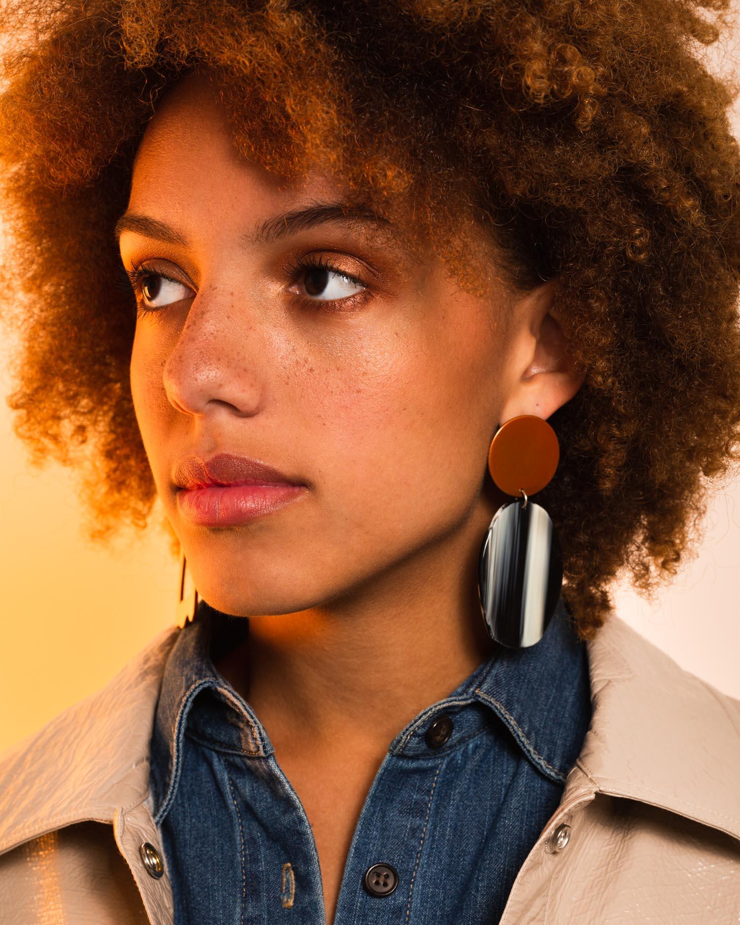 Aurora wears the  Geology Earrings in Tangelo Chrome