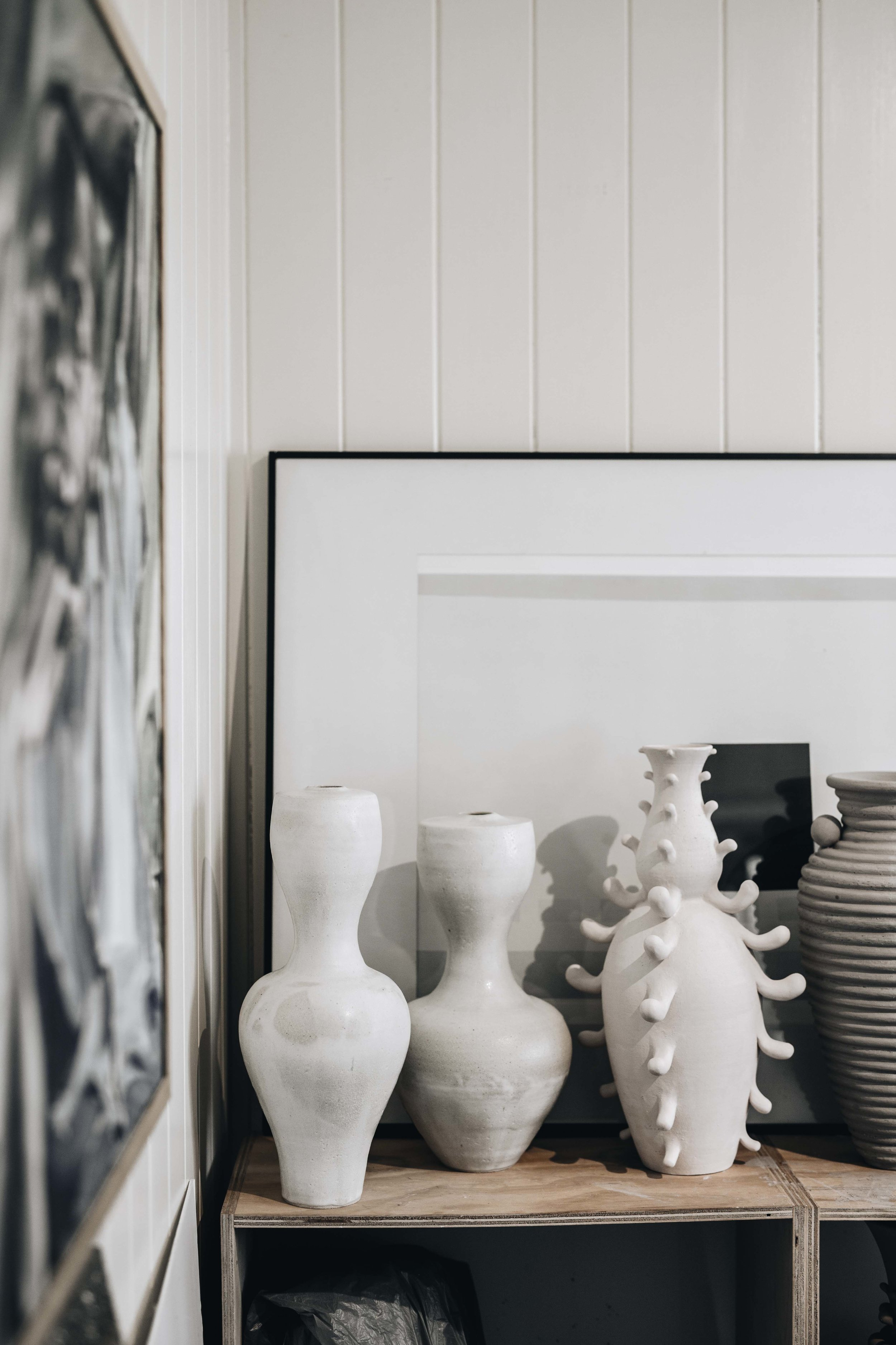 A collection of vessels by Nicolette sitting on the shelves in her studio.