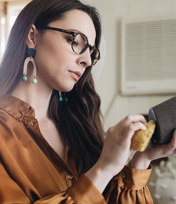Nicolette working on one of her symbol vases, wearing the    Pendulum Earrings.