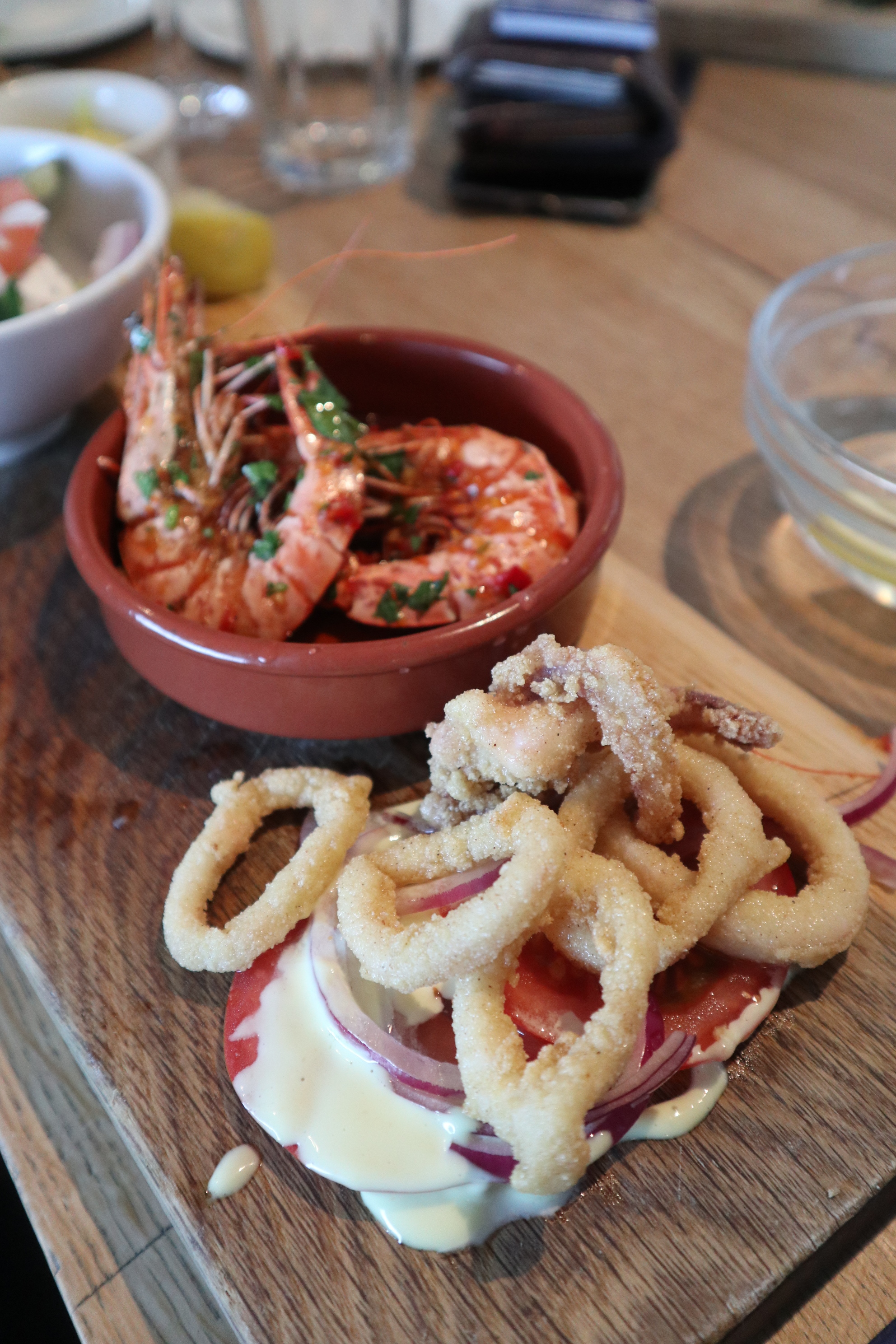 Tasting board at Rick Stein including padron peppers, chilli prawns, salt cod fitters, greek salad and calamari